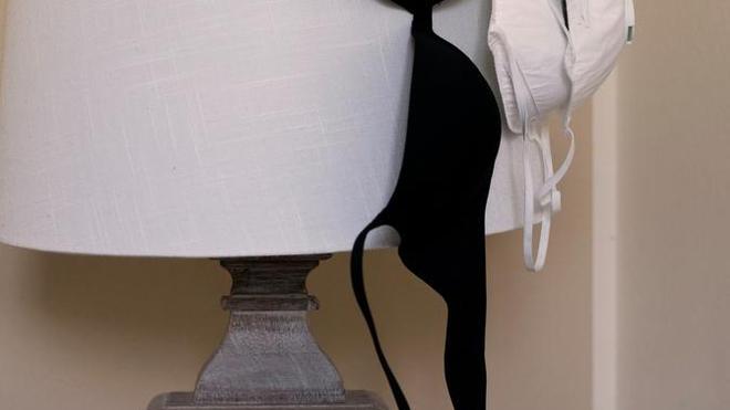 Deux masques de protection et un soutien-gorge suspendu à une lampe (photo d'illustration)