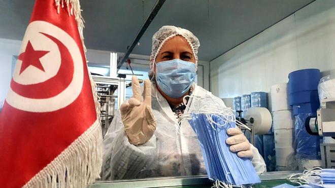 Une ouvrière qui est heureuse de fabriquer des masques pour les hôpitaux de son pays