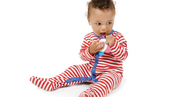 Bébé masse sa gencive avec son anneau de dentition