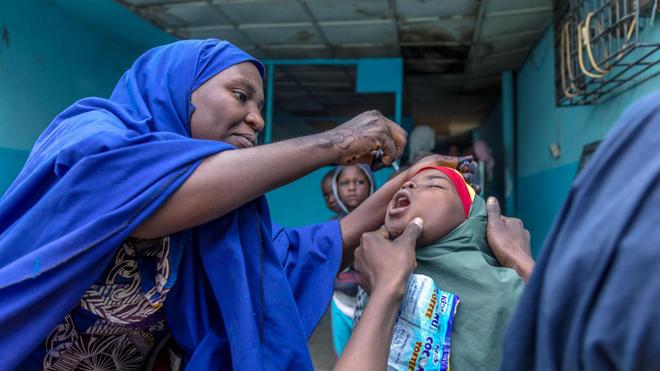 Un vaccinateur fournit à une jeune fille un vaccin oral contre la polio dans l'État de Kano, au Nigeria, en 2020